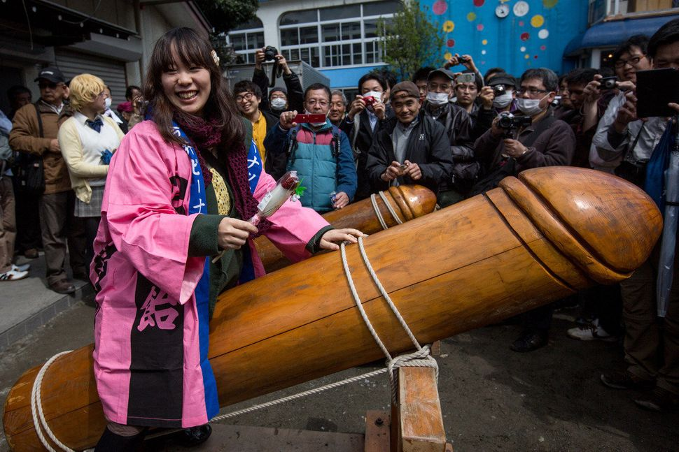 A woman poses for photographers as she straddles a large wooden phallic sculpture.