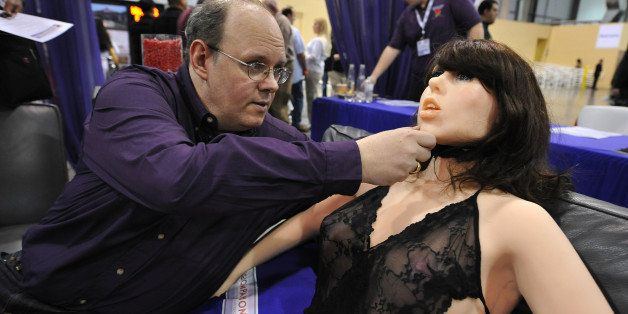 Engineer-inventor Douglas Hines adjusts the head of his company's 'True Companion' sex robot, Roxxxy, at the TrueCompanion.co