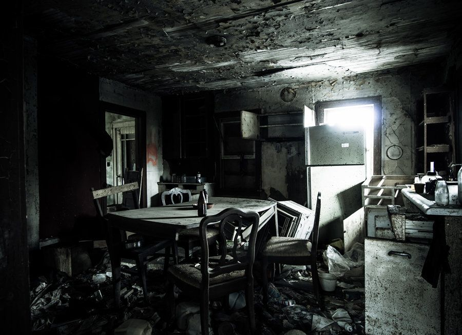 A decaying, crumbling kitchen complete with a table, left behind as if it were a time capsule.