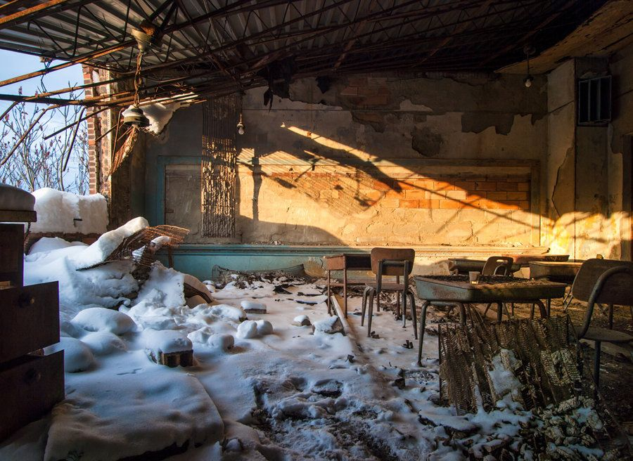 An abandoned country school. One wall has completely fallen, letting snow into the classroom.