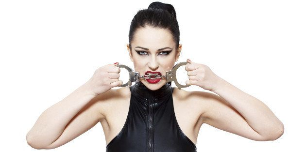 Sexy woman bite handcuffs, bdsm, isolated on white