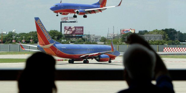 In this photo taken Friday, June 25, 2010  passengers traveling on Southwest Airlines watch as one plane waits to takeoff and