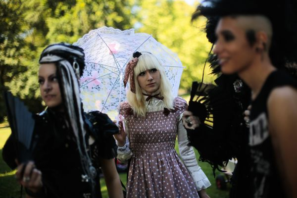 "Participants in the ""Victorian Picnic"" at the Wave Gothic Festival take a stroll in a park in Leipzig, central Germany, on Ju"