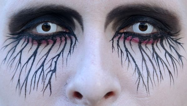 In this June 8,  2014. photo, a participant with painted face and special contact lenses arrives at the Wave Gothic Festival