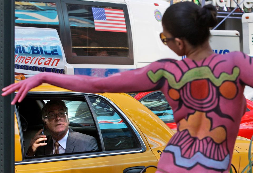A man in a cab looks at body painted model Bella Nabiyah as she poses for photographs in Times Square as part of an exhibit b