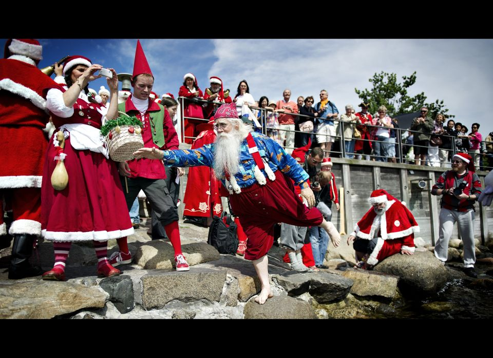 A Santa Claus from USA takes a foot bath at Copenhagen Harbour on July 18, 2011. About 120 Santas arrived in Copenhagen to pa