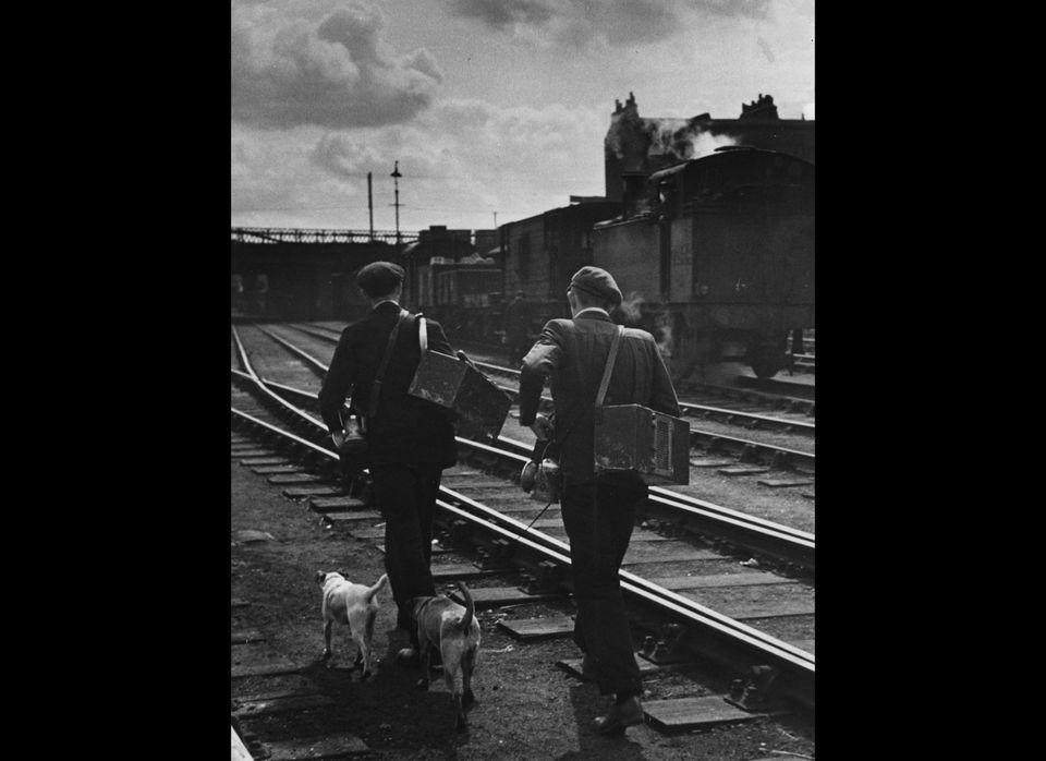 Railway rat catchers walk along the track.