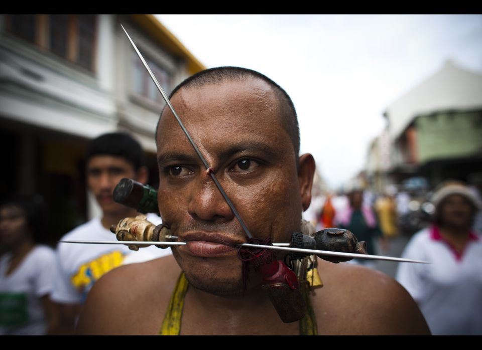 A devotee of the Chinese shrine of Kathu Shrine, pierces his cheeks with skewers during a procession of Vegetarian Festival o