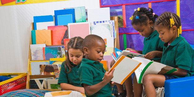Four preschool kids reading in classroom