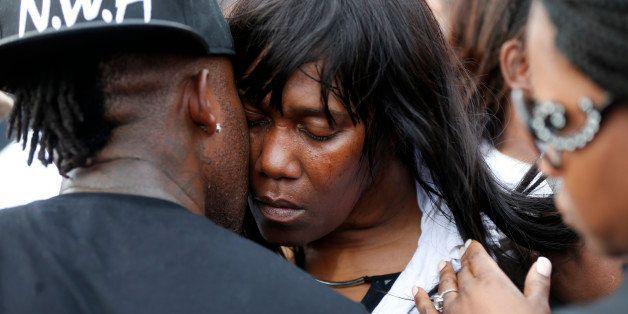 Sandra Sterling, aunt of Alton Sterling, is comforted at a vigil outside the Triple S convenience store in Baton Rouge, La.,