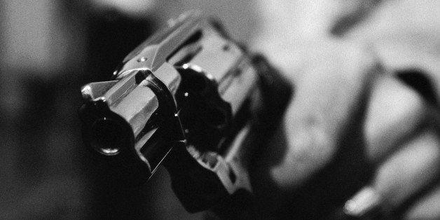Hand holding gun, close-up, b&w