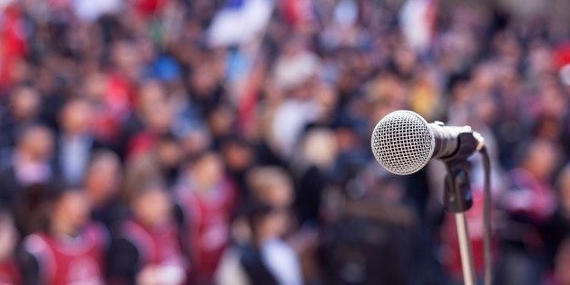 Microphone in focus against unrecognizable crowd