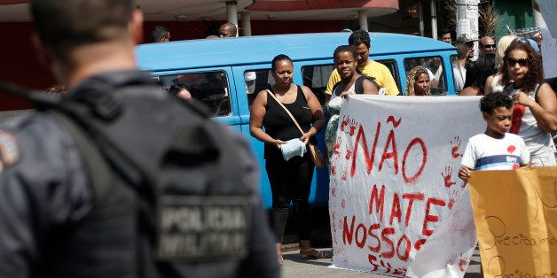 """Protesters hold a sign with a handwritten message that reads in Portuguese; """"Don't kill our children"""", in a march against pol"""