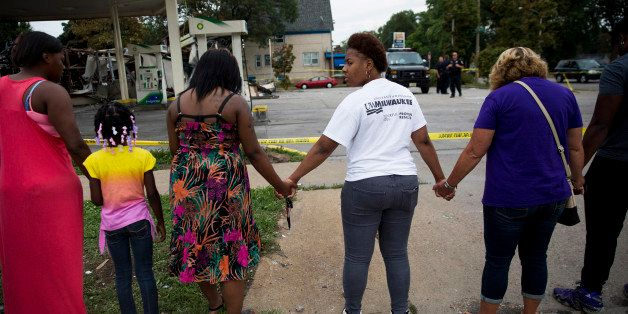 Jasmine Newson, 21, turns around while praying at a gas station that was destroyed by rioters after a fatal police shooting t