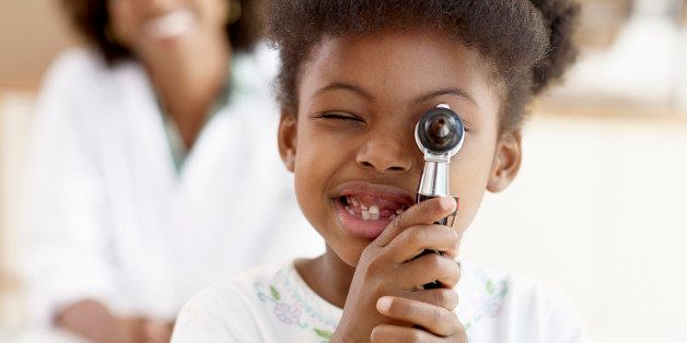 Girl (6-7) looking through otoscope, female doctor smiling background