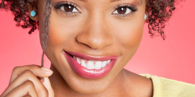 Portrait of an African American woman smiling over colored background