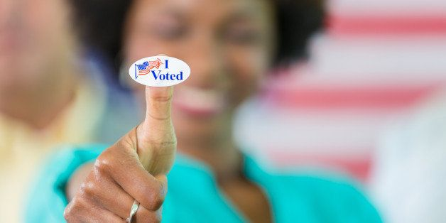 Smiling african american woman with an 'I voted' sticker on her thumb.