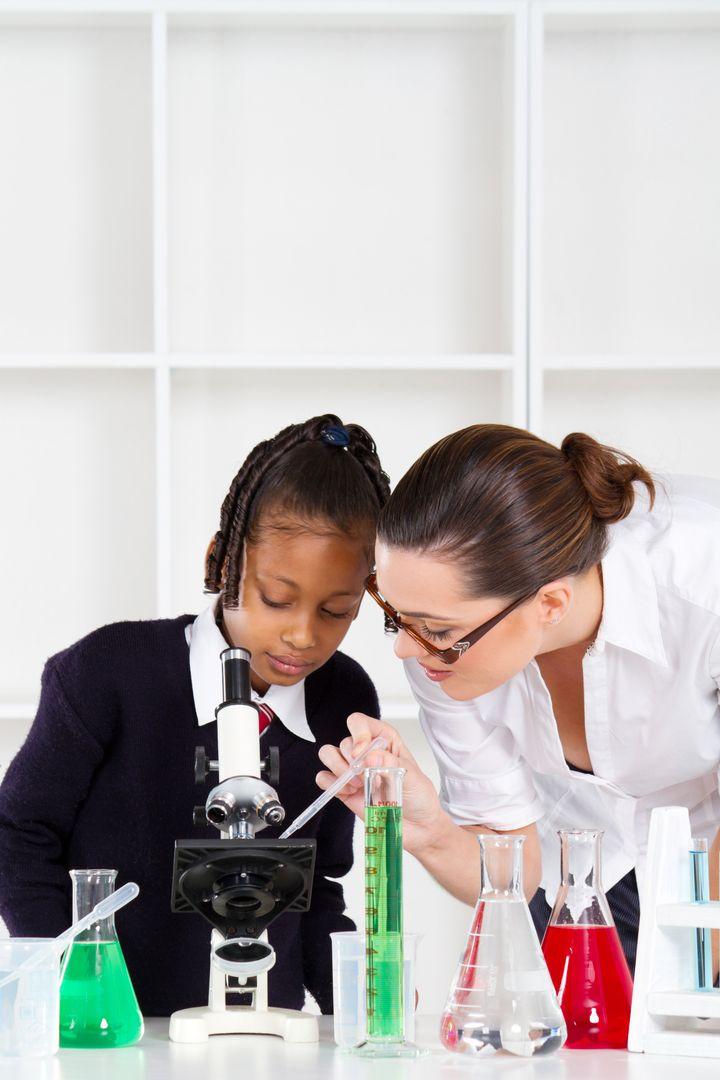 friendly teacher helping primary schoolgirl in science class
