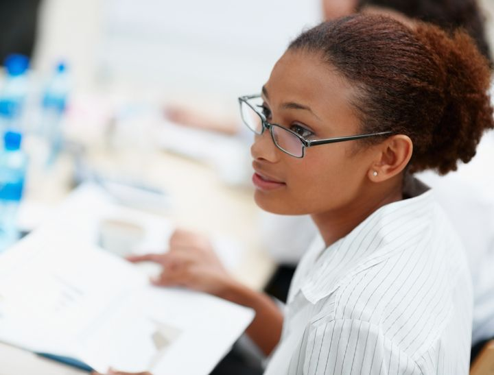 Young African American business woman with spectacles while at work