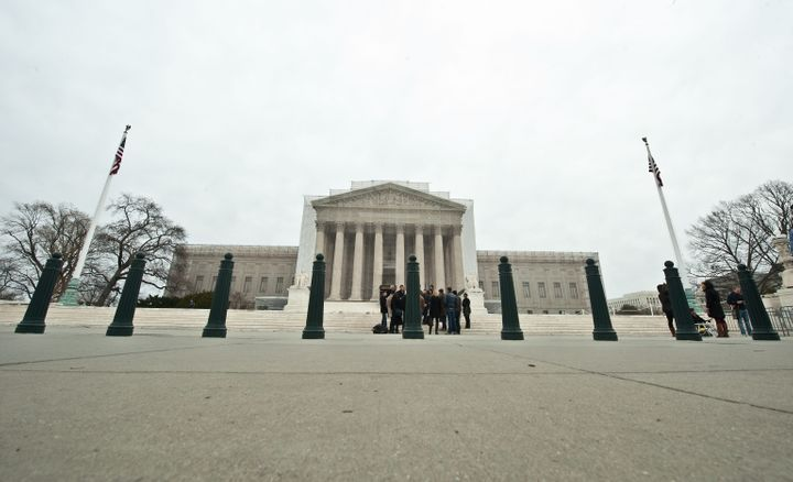 Tourists stand in front of the Supreme Court in Washington on March 24, 2013 as people begin lining up for the court's upcomi