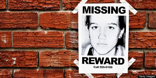 A 'Missing' poster of a teenage girl, offering a reward,  is taped to a red brick wall, possibly in a police station. The pho
