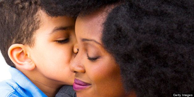A young boy kisses his Mom on the cheek.