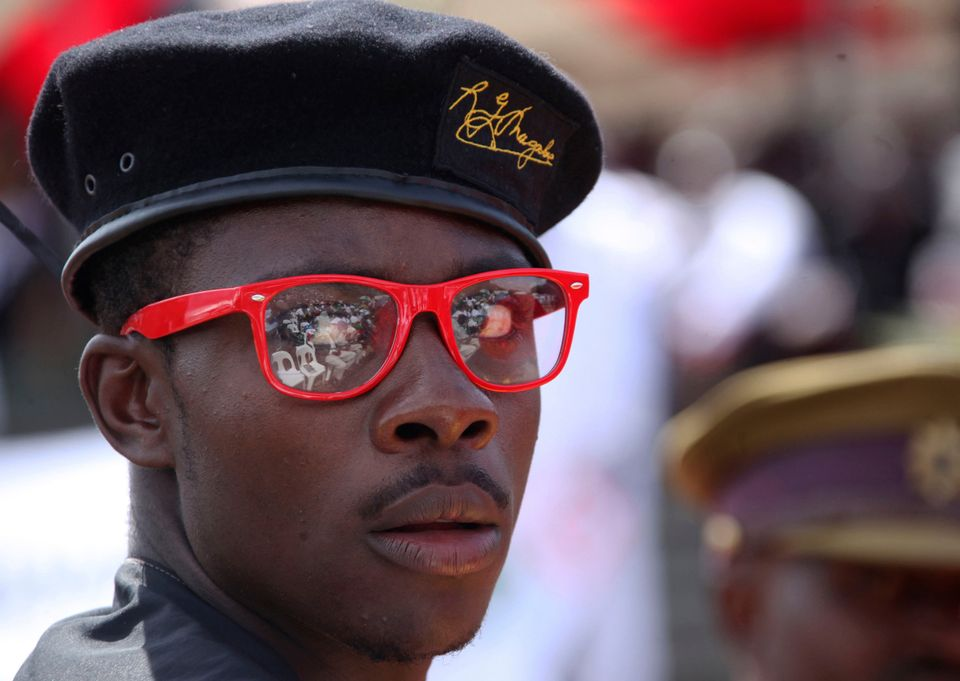 A man wears a President Robert Mugabe designer label beret, at the burial of Deputy President John Nkomo, at the Heroes Acre,