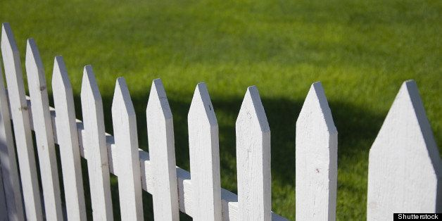 white picket fence with green...
