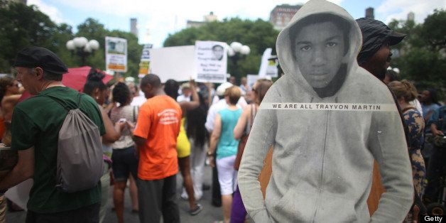NEW YORK, NY - JULY 14:  People gather at a rally honoring Trayvon Martin with his photo standing (R) while being held by a m