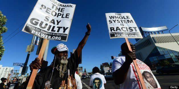 People hold placards and shout slogans during a rally at Leinert Park Los Angeles in the aftermath of George Zimmerman's acqu