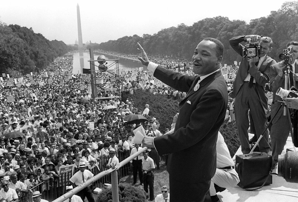U.S. civil rights leader Martin Luther KIng (C) waves to supporters from the steps of the Lincoln Memorial on August 28, 1963