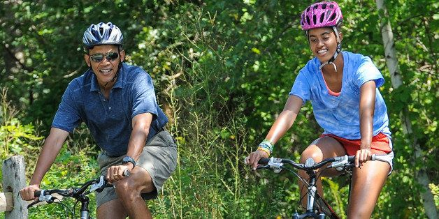WEST TISBURY , MA - AUGUST 16: U.S. President Barack Obama (L) his daughter Malia Obama ride a bike during a vacation on Mart