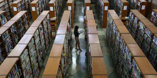 A college student looks at a book between the aisles at the Kyung Hee University Central Library on the university's campus i