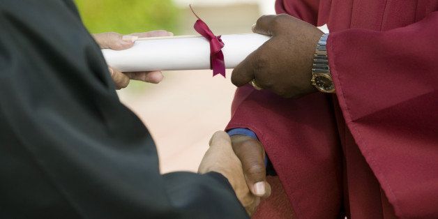 graduate receiving diploma and...