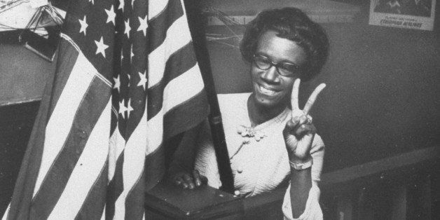 1st black female member of Congress, Shirley Chisholm, holding up two fingers in victory sign while standing behind large Ame