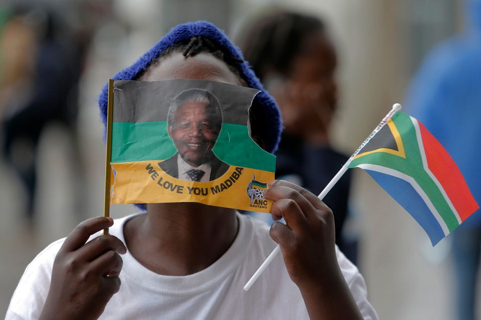 A girl covers her face with a flag bearing the image of Nelson Mandela outside of the memorial service for former South Afric