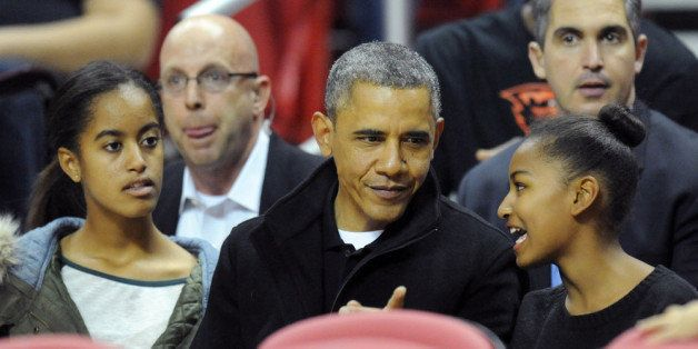 COLLEGE PARK, MD - NOVEMBER 17:  US President Barack Obama with his daughters Malia (L) and Sasha (R) in their seats before a
