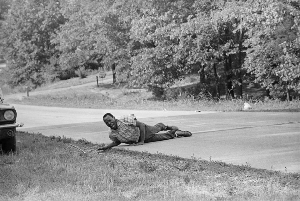 Civil rights activist James Meredith grimaces in pain as he pulls himself across Highway 51 after being shot in Hernando, Mis