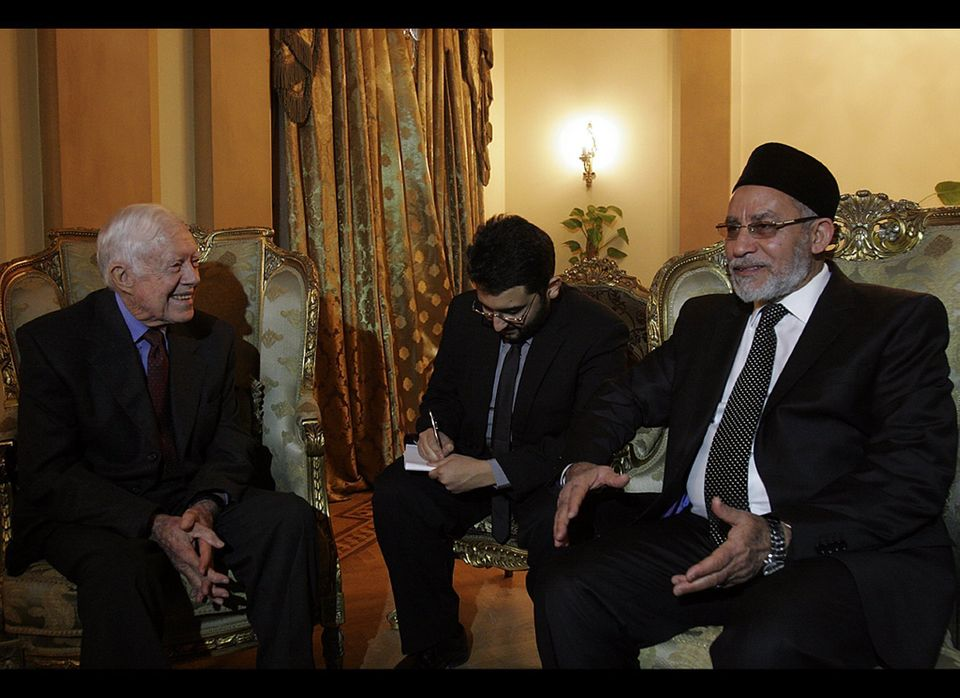 Mohammed Badie, head of Egypt's Muslim Brotherhood, (R) speaks with former US president Jimmy Carter during a meeting in Cair