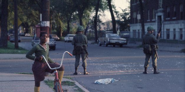 National Guardsmen stand guard as a young boy pauses from riding his bicycle in the west side neighborhood of Lawndale, Chica