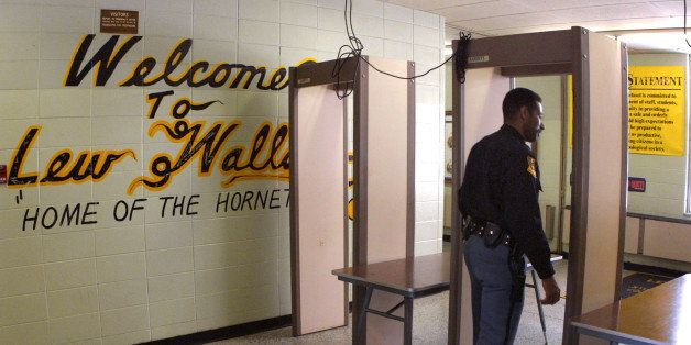 387319 02: Police Officer Jeff Tatum passes through a metal detector at Lew Wallace High School March 30, 2001 in Gary, IN af