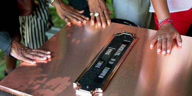 ST. LOUIS, MO - AUGUST 25: Family members touch the copper top of the vault containing the casket of Michael Brown during bur