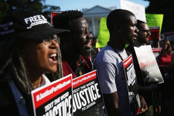 Demonstrators shout slogans as they gather in front of the White House to deliver nearly 950,000 signatures August 28, 2014 i