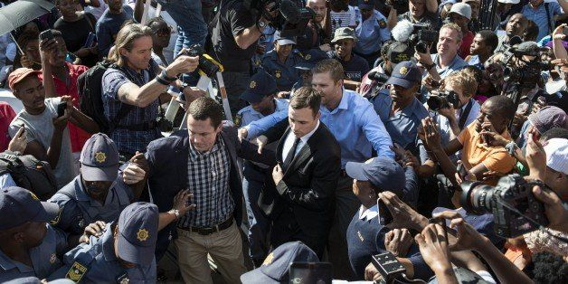 South African Paralympic athlete Oscar Pistorius (C) is surrounded by members of the media as he leaves the High Court after
