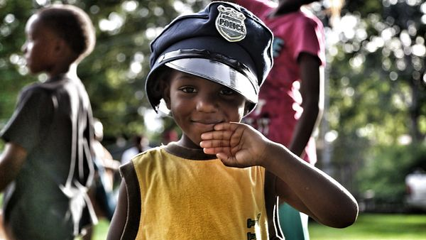 A young boy wears a toy police hat during a protest on Canfield Drive on Aug. 23. A number of children were playing with toy