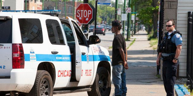 CHICAGO, IL - JUNE 9: Chicago police wearing bulletproof vests handcuff a young man temporarily while they check his informat