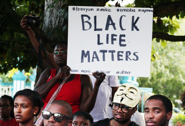 People in a crowd hold signs and listen to speakers at a demonstration on Thursday, Aug. 14, 2014, in Decatur, Georgia, in th