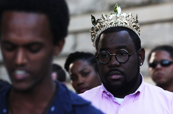 An unidentified man wearing a crown listens as a speaker addresses the crowd on Thursday, Aug. 14, 2014, in Decatur, Georgia.