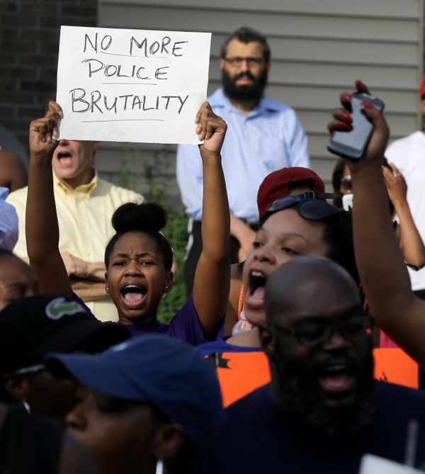 Demonstrators peacefully gather Thursday, Aug. 14, 2014, at the site where Michael Brown was shot and killed by police in Fer