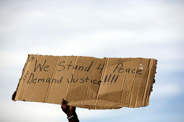 A demonstrator holds up a sign Thursday, Aug. 14, 2014, at the site where Michael Brown was shot and killed by police in Ferg